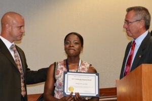 Middlesex County Freeholder Director Ron Rios presents a certificate and the 2015 NJAC Foundation Scholarship check from Investors Bank to Shakyran Gaskin, who plans to study psychology at Kean University.